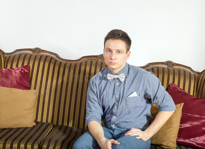 Young man posing seated on a sofa at home. Male model sitting on couch at home. Serious person in shit and bow tie resting on an old retro classic furniture royalty free stock photography