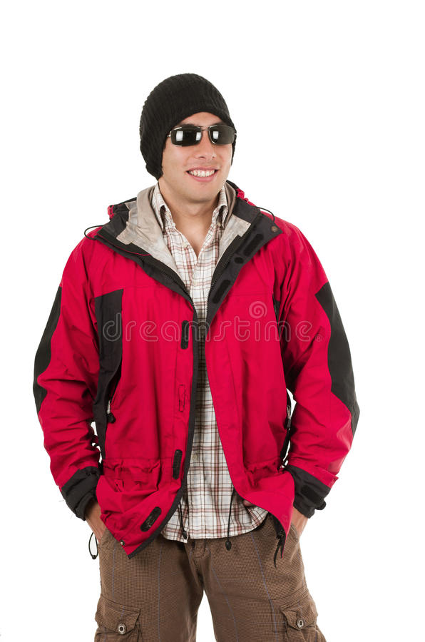 Young man posing wearing red winter coat. Handsome man posing wearing red winter coat and sunglasses with hands in pockets isolated on white stock image