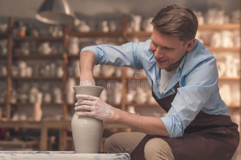 Young man at the potter`s wheel. Indoors stock photo