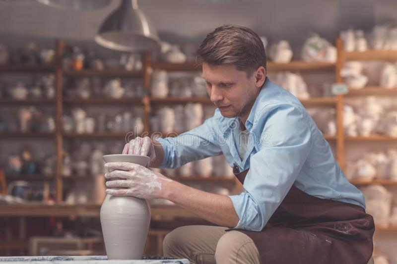 Young man with a potter`s wheel. In pottery stock photo
