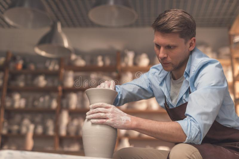 Young man at a potter`s wheel. In workshop stock image