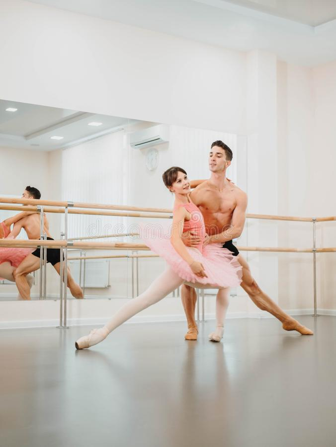 Young man practicing in classical ballet in the gym or ballet hall. Minimalism interior, royalty free stock images