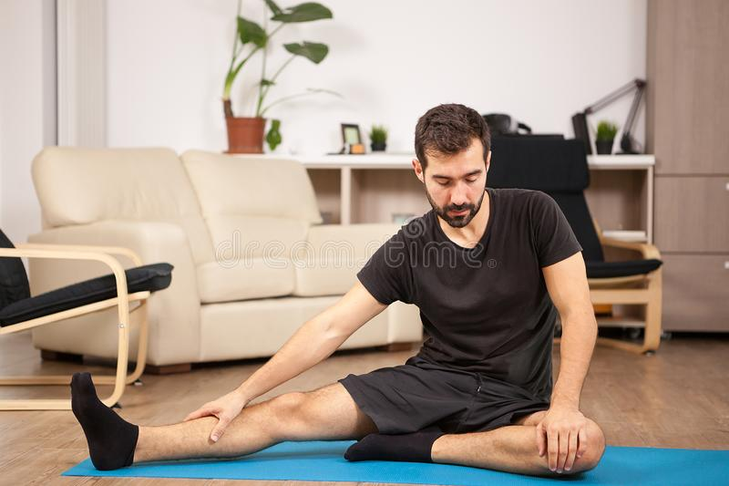 Young man practicing yoga in his living room royalty free stock image