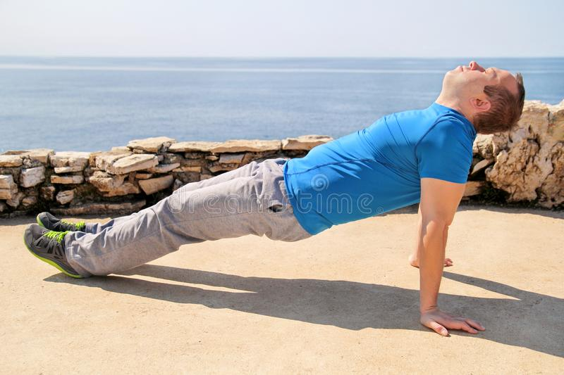 A young man practicing yoga, pilates and stretching on a seashore. Handsome man is doing stretching exercises on the beach. stock photos