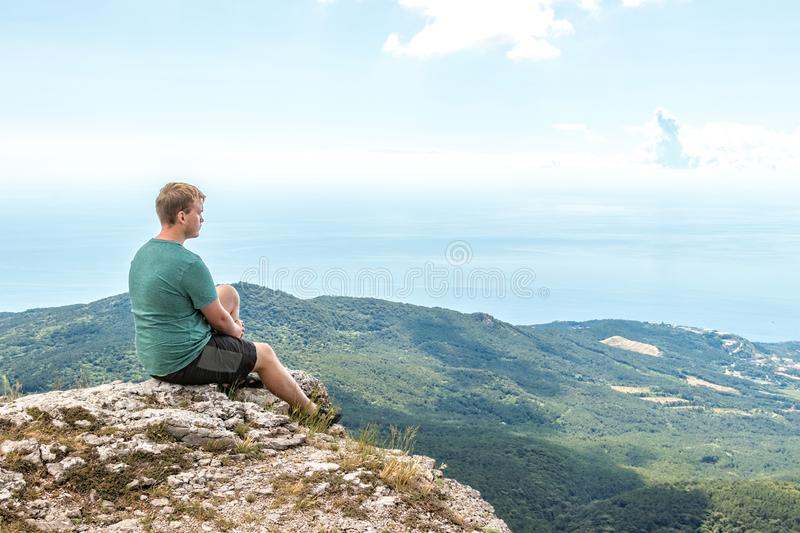 Young man practicing yoga pose sitting on the rocky peak. Man do meditation and enjoying view royalty free stock image