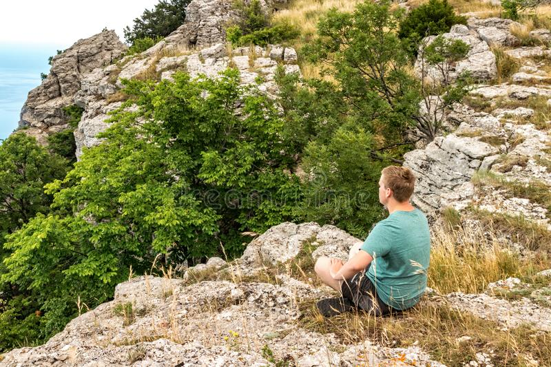 Young man practicing yoga pose sitting on the rocky peak. Man do meditation and enjoying view royalty free stock images