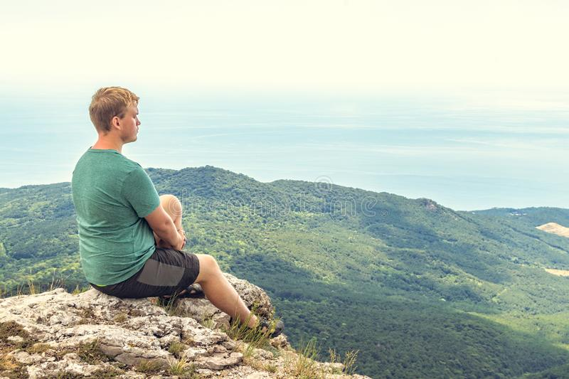 Young man practicing yoga pose sitting on the rocky peak. Man do meditation and enjoying view stock photo