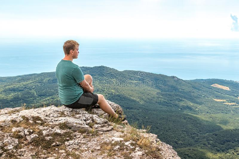 Young man practicing yoga pose sitting on the rocky peak. Man do meditation and enjoying view royalty free stock photography