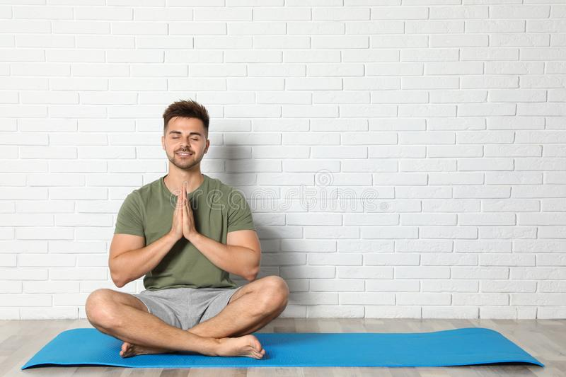Young man practicing zen yoga near white brick wall, space for royalty free stock images