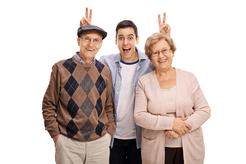 Young man pranking a mature man and woman with bunny ears. Young men pranking a mature men and women with bunny ears isolated on white background stock photos