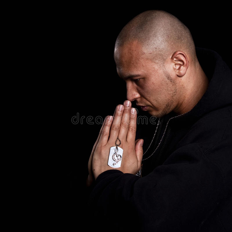Young man praying. A young asian man with a hoddie is praying over black stock photography