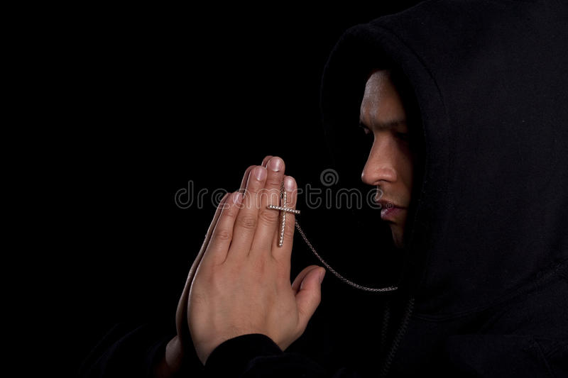 Young man praying. A young asian man with a hoddie is praying over black royalty free stock photos