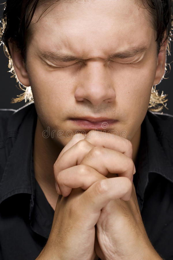 Young man praying. Closeup portrait of a young man praying to god stock photos