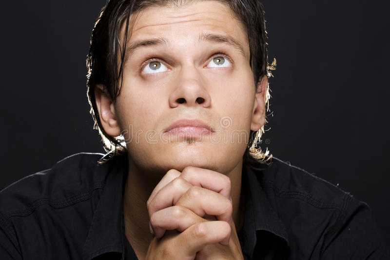 Young man praying. Closeup portrait of a young man praying to god royalty free stock image