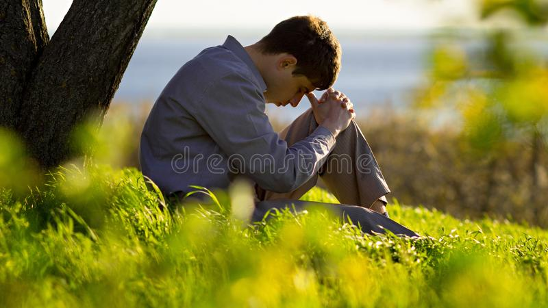 Young man praying to God in the nature bowing his head to his knees, concept religion. Young man praying to God near a tree in the nature bowing his head to his royalty free stock photo