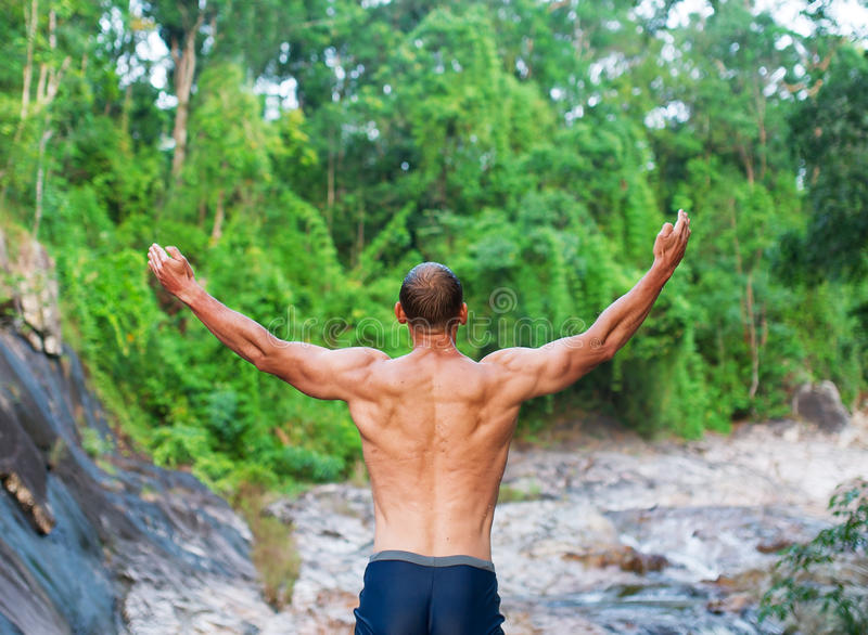 The young man prays to god and enjoys beauty of the nature. A young man standing on the bank of the mountain river and admiring the nature around stock photos