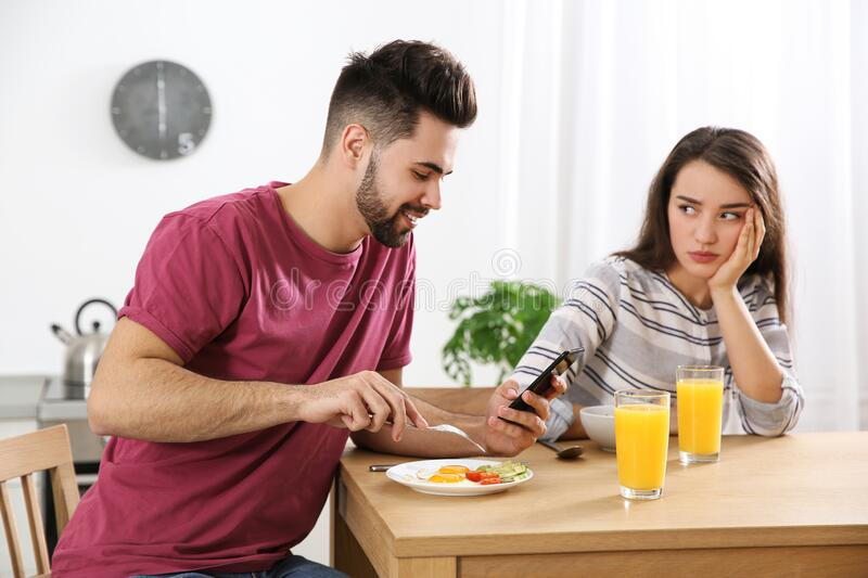 Young man preferring smartphone over his girlfriend royalty free stock photo