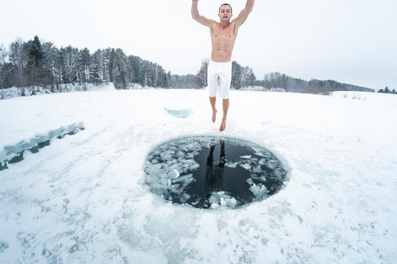 Young man prepares to swim in the ice hole stock photo