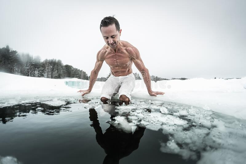 Young man prepares to swim in the ice hole royalty free stock photo