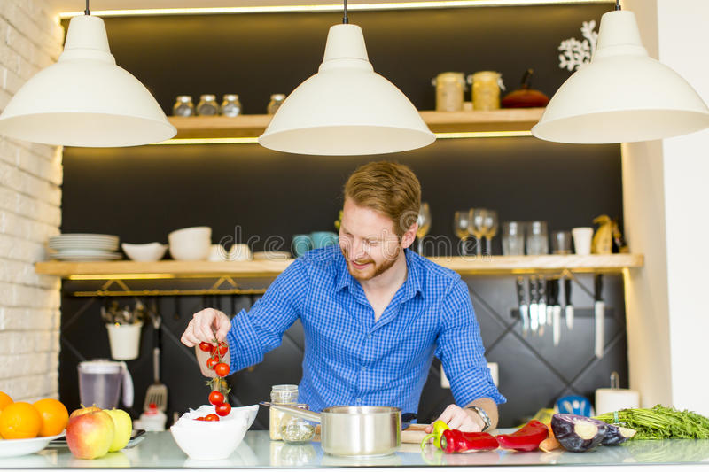 Young man preparing healthy food. In the modern kitchen royalty free stock image
