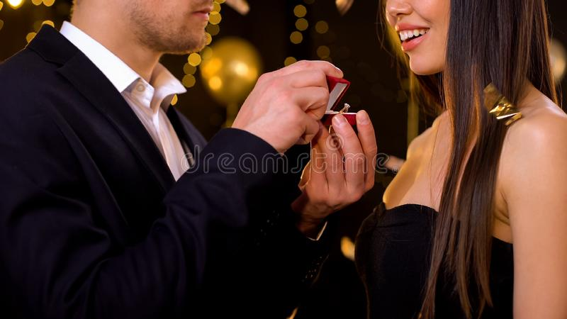 Young man presenting diamond ring to girlfriend, proposing at party, marriage. Young men presenting diamond ring to girlfriend, proposing at party, marriage stock photos