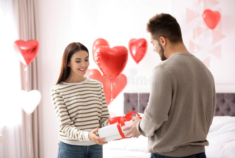 Young man presenting gift to his girlfriend in bedroom decorated with heart balloons. Valentine`s day celebration. Young men presenting gift to his girlfriend in royalty free stock image