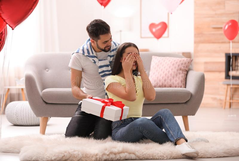 Young man presenting gift to his girlfriend in room decorated with heart shaped balloons. Valentine`s day celebration royalty free stock image