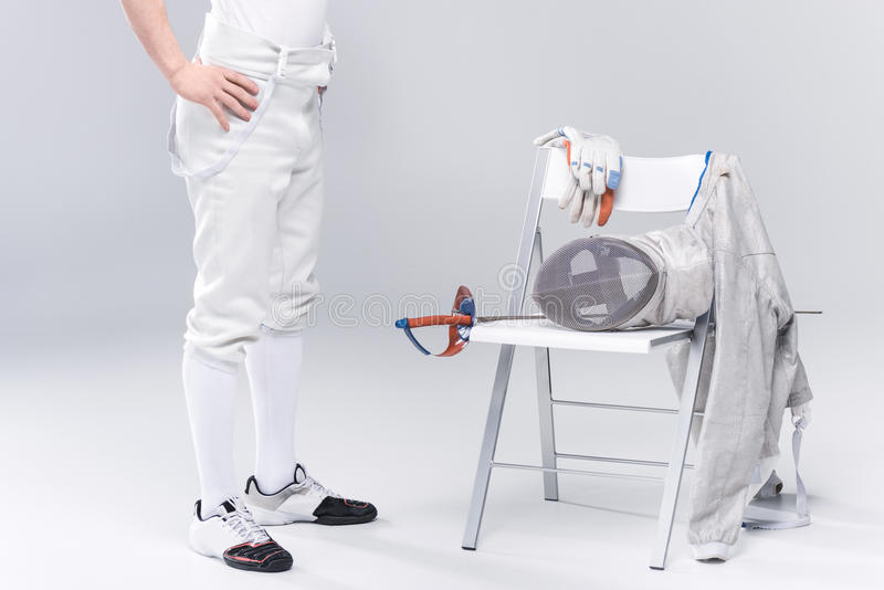 Young man professional fencer standing near chair with fencing equipment royalty free stock photo