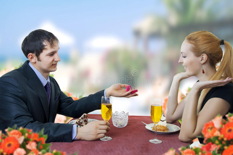 Young man propose marriage to woman in restaurant. stock photos