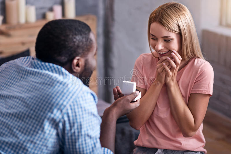 Young man proposing marriage to his girlfriend. Be mine. Young African handsome men proposing marriage and giving a ring to his beautiful girlfriend while she stock photography
