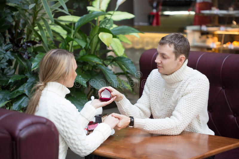 Young man proposing to girlfriend offering. Young men proposing to girlfriend offering engagement ring stock photo