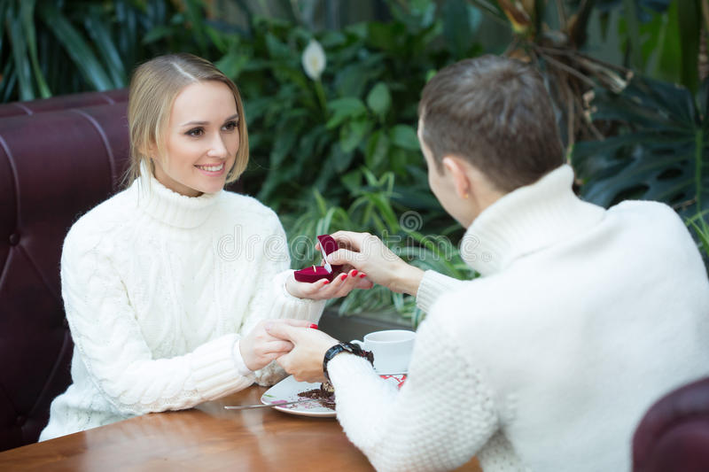 Young man proposing to girlfriend offering. Young men proposing to girlfriend offering engagement ring royalty free stock photo