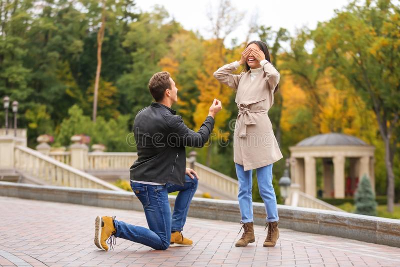 Young man proposing to his beloved in autumn park. Young men proposing to his beloved in autumn park royalty free stock image