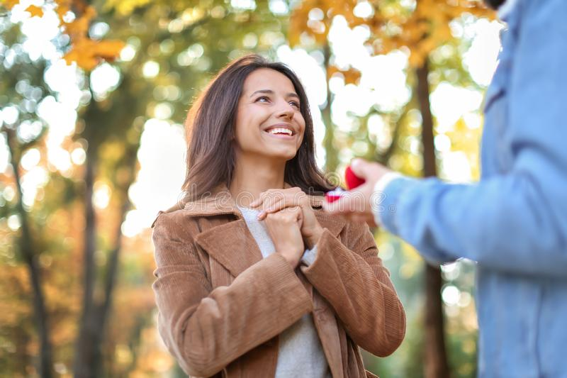 Young man proposing to his beloved in autumn park royalty free stock image