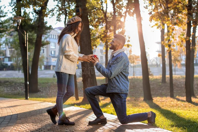 Young man proposing to his beloved in autumn park. Young men proposing to his beloved in autumn park stock photos