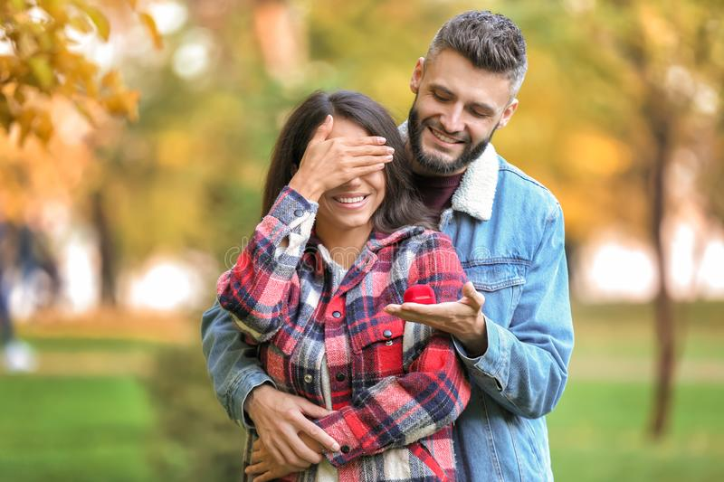 Young man proposing to his beloved in autumn park. Young men proposing to his beloved in autumn park stock photography