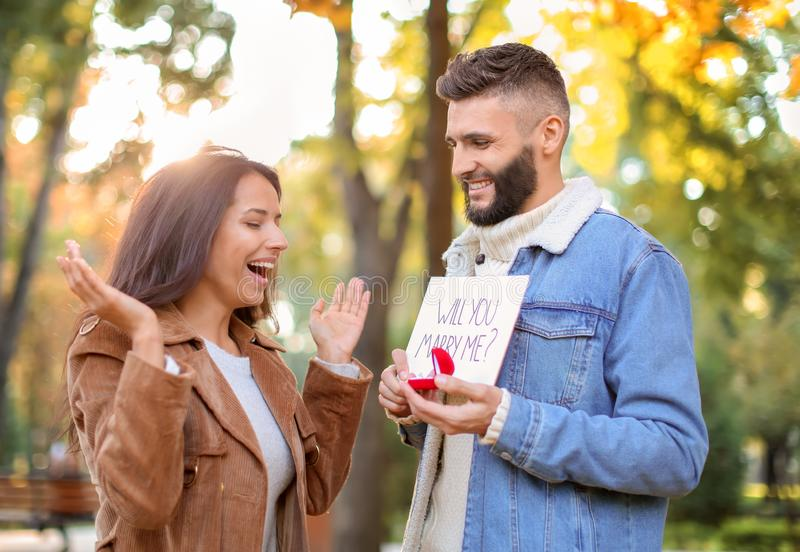 Young man proposing to his beloved in autumn park stock photos