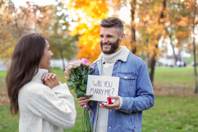 Young man proposing to his beloved in autumn park royalty free stock images