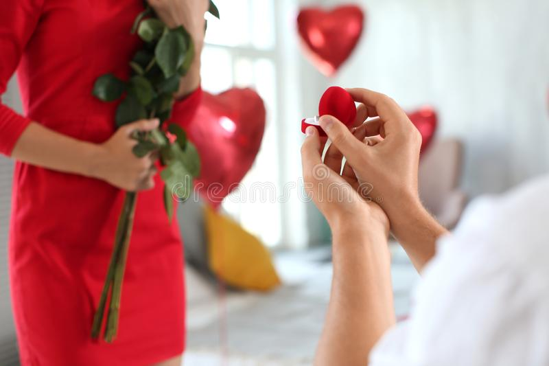 Young man proposing to his beloved with beautiful engagement ring at home stock images