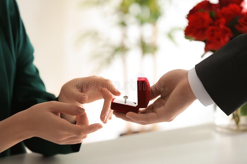 Young man proposing to his beloved at romantic date stock image