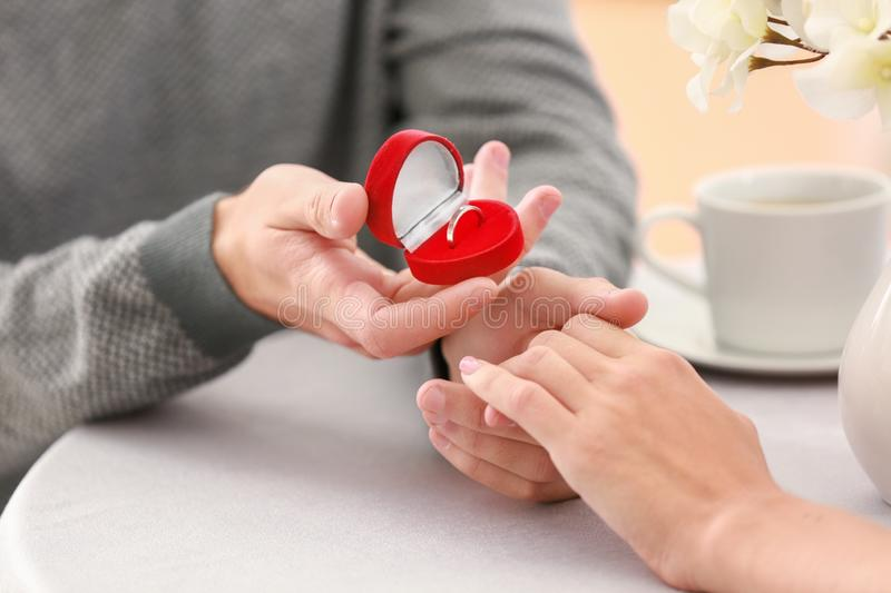 Young man proposing to his beloved on romantic date, closeup stock photography