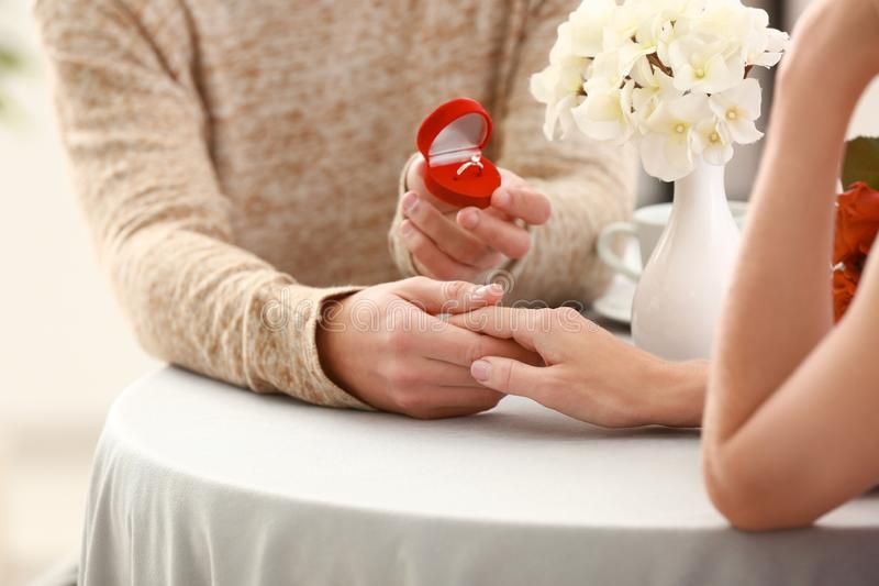 Young man proposing to his beloved on romantic date, closeup royalty free stock photo