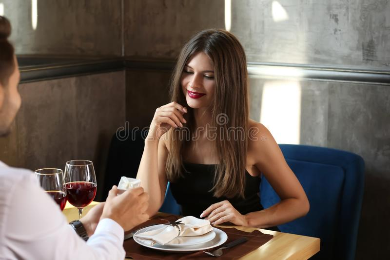 Young man proposing to his beloved on romantic date in restaurant. Young men proposing to his beloved on romantic date in restaurant royalty free stock image