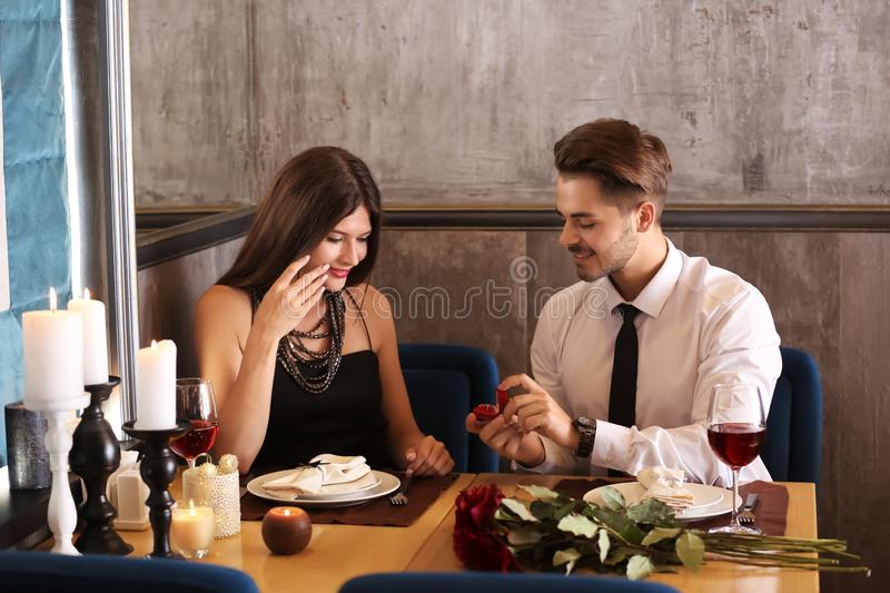 Young man proposing to his beloved on romantic date in restaurant. Young men proposing to his beloved on romantic date in restaurant royalty free stock photography