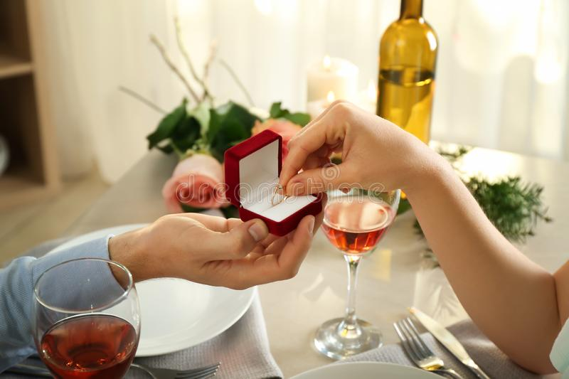 Young man proposing to his beloved at romantic date in restaurant stock photos