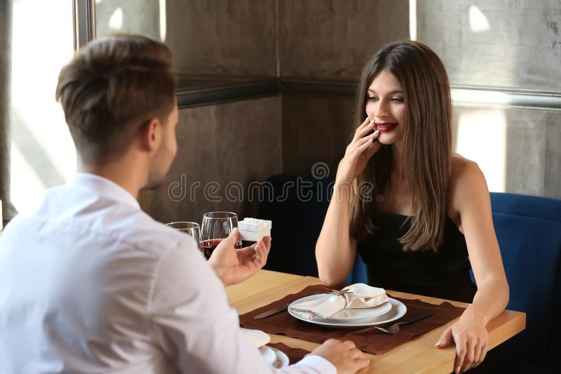 Young man proposing to his beloved on romantic date in restaurant. Young men proposing to his beloved on romantic date in restaurant stock photos
