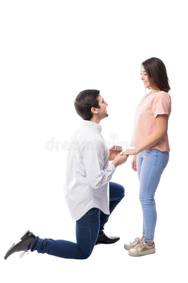 Young man proposing to his girlfriend. Profile view of a young men kneeling in front of his girlfriend and making a marriage proposal with a ring stock photos