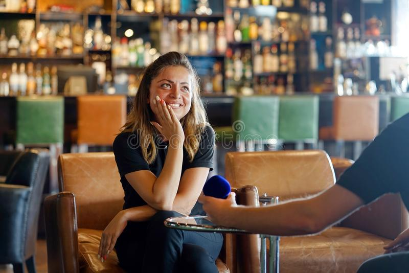 A man makes a proposal to marry the waitress at the bar. Young man proposing to waitress girlfriend to marry, engagement ring box. Lady hesitating, having doubt stock photos