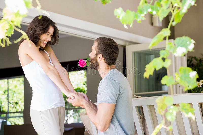 Young man proposing a woman with a flower. Young men proposing a women with a flower at home stock photo