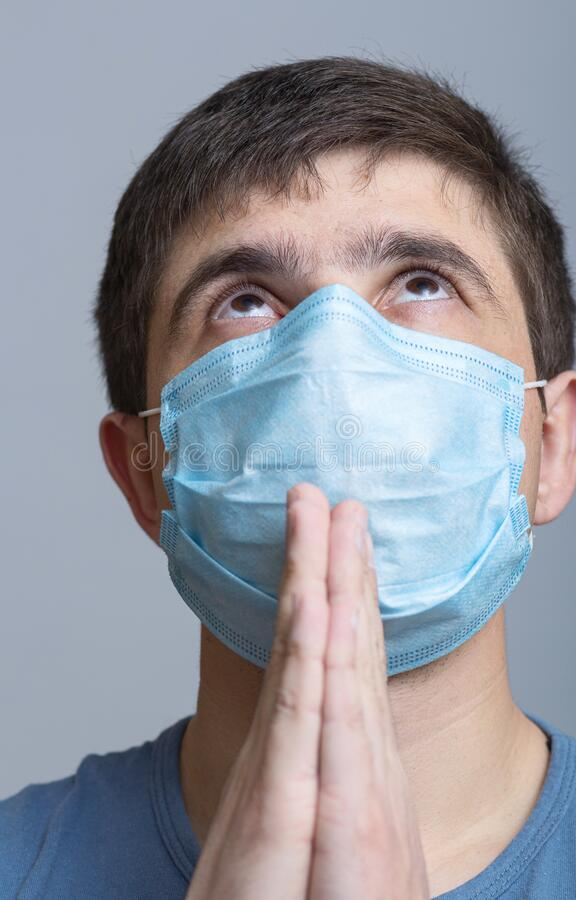 Young man in a protective medical mask folded hands near chin and looking up with faith on studio backgroung, pleading for help,. Gratitude to God, concept royalty free stock photography